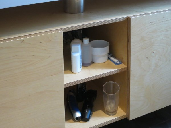 Met ruimte voor handdoeken achter de deur links en toiletspullen in het open vak …