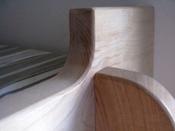 Bed wordt deels ondersteund door de kast en de trap en is deels aan de muur bevestigd